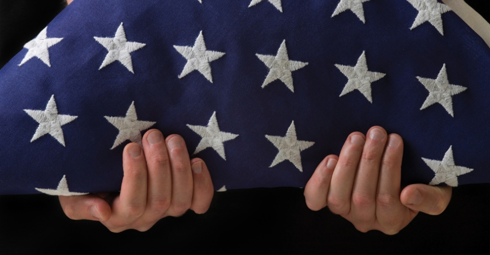 Image of person holding folded flag