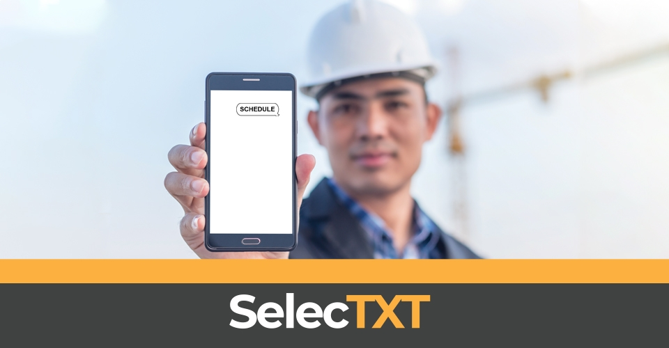 Construction worker holding up cell phone